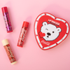 Physicians Formula   Coca-Cola 3 Piece Lip Balm Tin   Products front facing scattered out of tin with caps fastened, with pink background