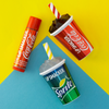 Coca-Cola 3 Pack Beverage Lip Balm- Coke & Sprite | Lip Smacker | Products angled caps fastened, with yellow and blue background