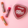 Lip Smacker | Dr Pepper 3 Piece Lip Balm Tin | Products front facing scattered caps fastened, with pink background