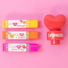 Lip Smacker | 3 Piece Lip Balm with Heart Topper - Red | Product front facing out of tube caps fastenend, with pink background
