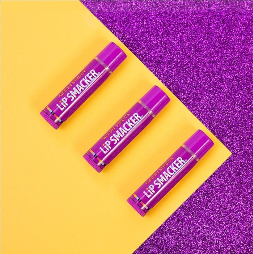 Grape flavored Lip Balm pictured on yellow and purple background