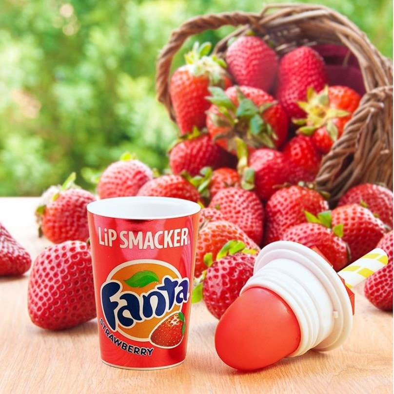 Fanta Strawberry flavored lip balm pictured with a basket of strawberries