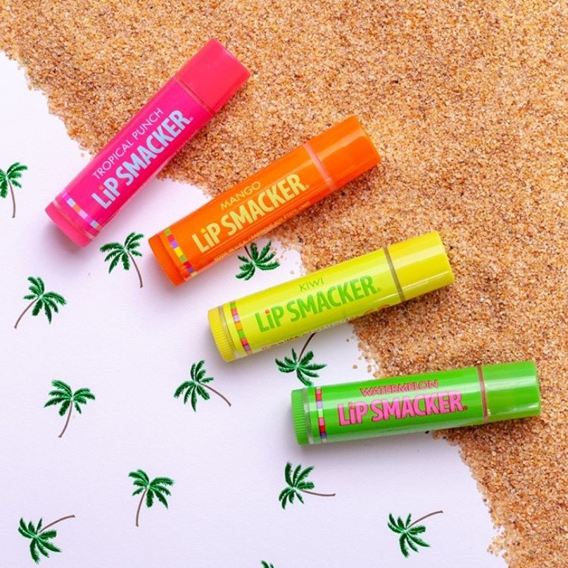 Tropical Flavor Lip Balms in mango, kiwi, watermelon, and tropical punch flavors pictured against sand and palm trees