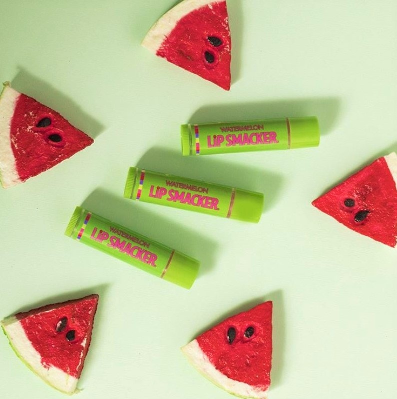 Watermelon Flavored Lip Balms pictued next to watermelon slices